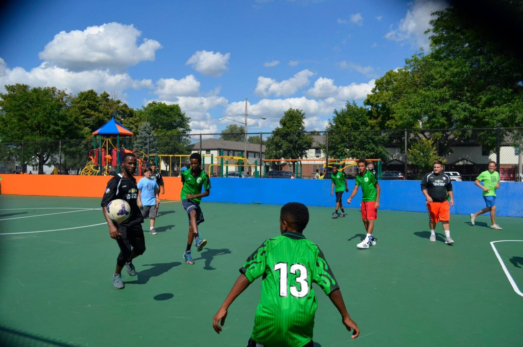 Kids playing soccer on newly renovated box soccer court at Skiddy Park.