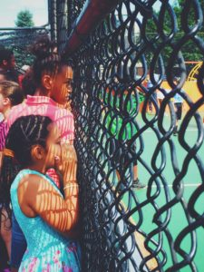 Skiddy Park soccer court with children watching players on the field separated by a chain link fence