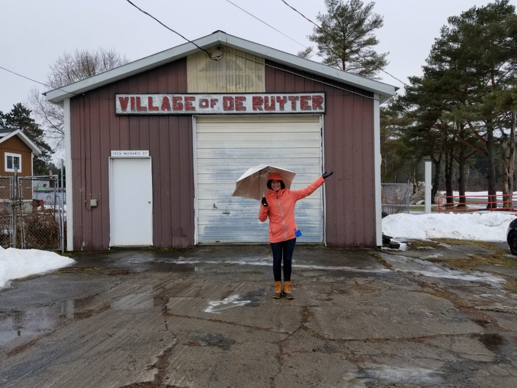 Lerner Fellow Jordana Gilman poses with an umbrella, outside under the Village of DeRuyter sign