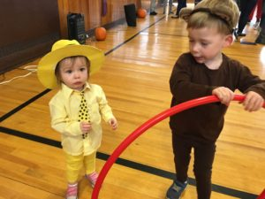 Two brothers dressed as the chracters from curious george. The smaller child wears bright yellow pants and yellow button down, with a pok-a-dot tie and a bright yellow fedora. His older brother stands a few steps way wearing brown jumpsuit and monkey ears while playing with a red hula hoop.